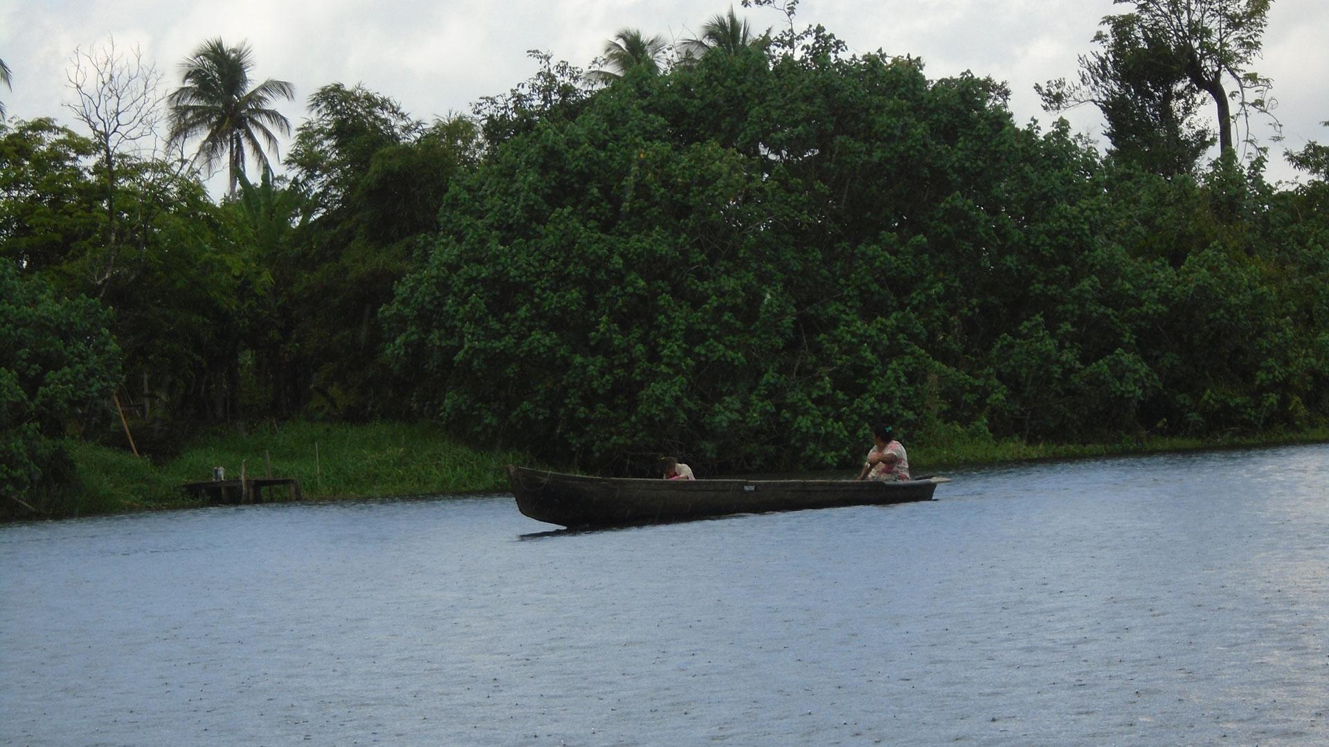 Una mujer indígena rama junto a su hijo navegando en el Río Indio.