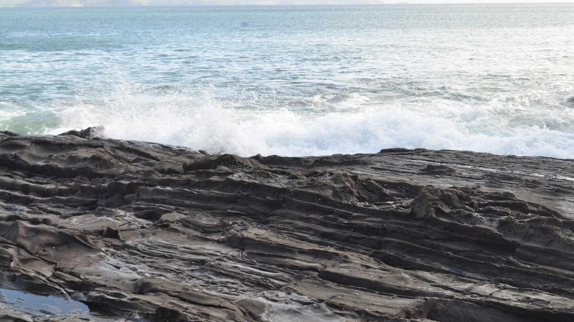 El mar choca contra las rocas produciendo el sonido de bravura del océano.